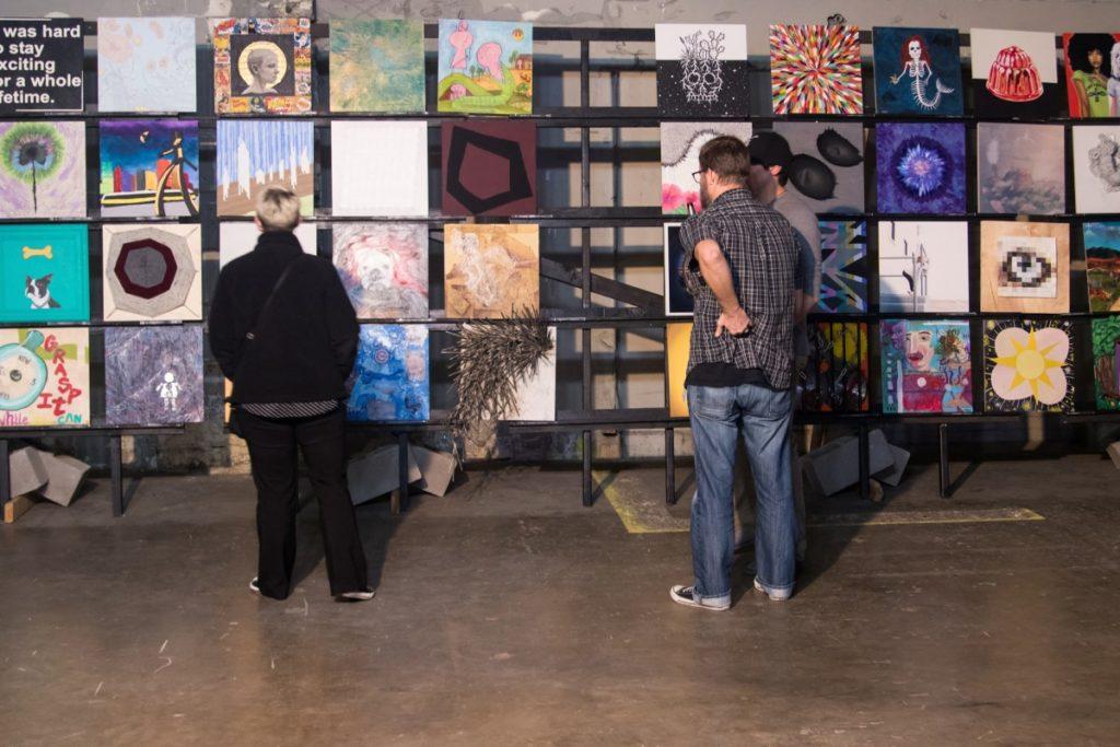 Two people viewing paintings on display