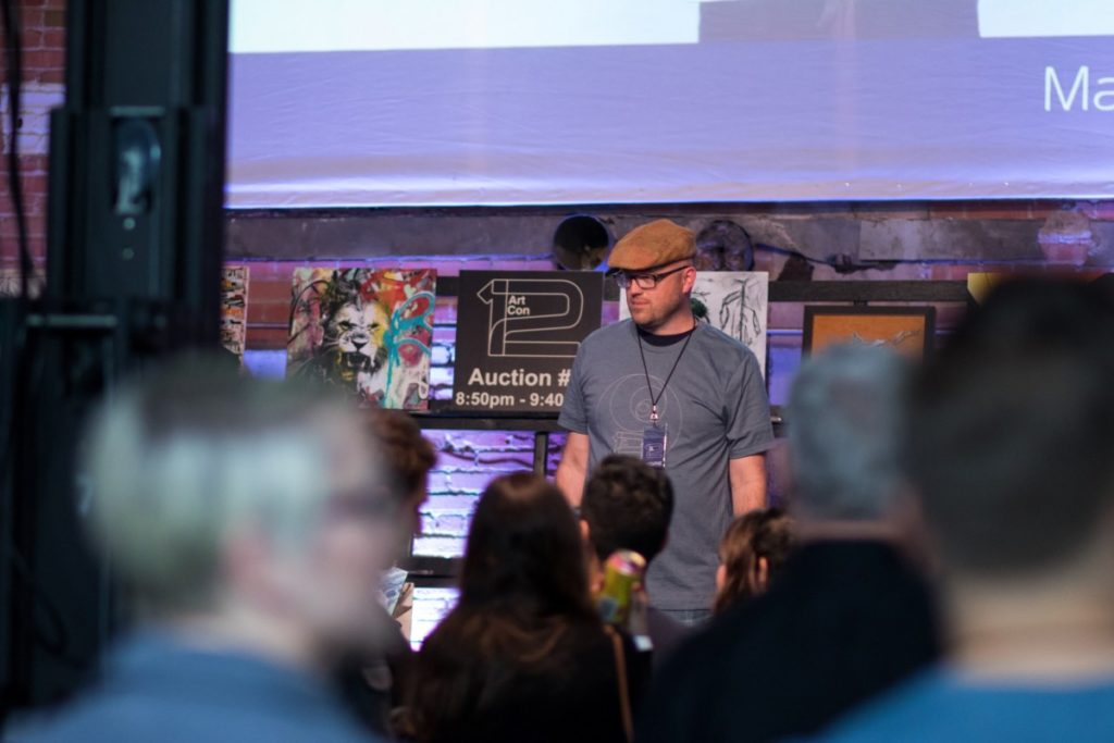 Man auctioning off paintings
